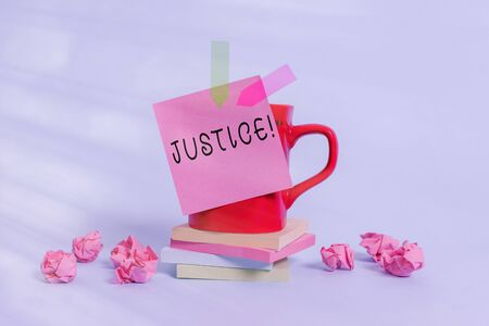 Conceptual hand writing showing Justice. Concept meaning impartial adjustment of conflicting claims or assignments Coffee cup sticky note banners paper balls pastel background