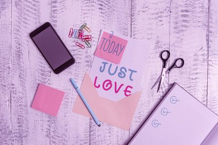 Text sign showing Just Love. Business photo showcasing being interested physically in someone An emotional attachment Envelope sheet smartphone notes pen notepad clips scissors wooden back 版權商用圖片