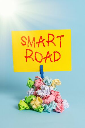 Word writing text Smart Road. Business photo showcasing number of different ways technologies are incorporated into roads Reminder pile colored crumpled paper clothespin reminder blue background