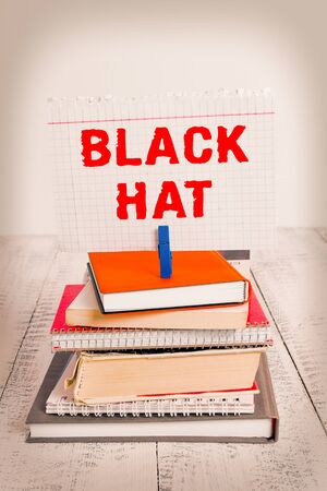 Writing note showing Black Hat. Business concept for used in reference to a bad demonstrating especially a villain or criminal pile stacked books notebook pin color reminder white wooden