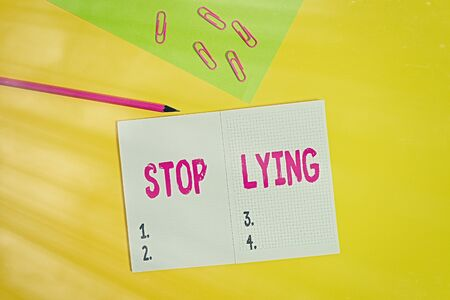 Text sign showing Stop Lying. Business photo showcasing put an end on chronic behavior of compulsive or habitual lying Blank paper sheet pencil clips smartphone two notepads colored background