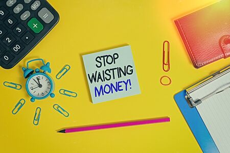 Text sign showing Stop Wasting Money. Business photo text advicing demonstrating or group to start saving and use it wisely Alarm clipboard calculator wallet clip band pencil notepad color background