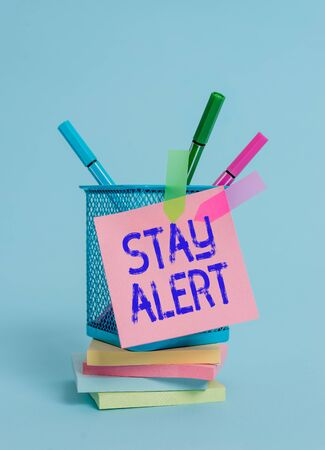 Text sign showing Stay Alert. Business photo text Paying full attention to things around Quick to see or understand Sticky note arrow banners stacked pads metal pens holder pastel background Stock Photo