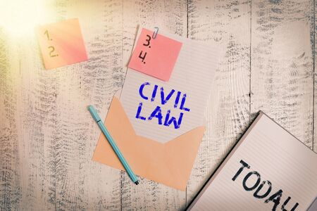 Writing note showing Civil Law. Business concept for Law concerned with private relations between members of community Envelope sheet letter paper sticky notes pen notepad wooden background