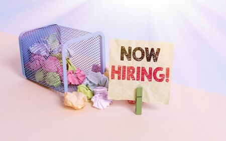 Writing note showing Now Hiring. Business concept for finding evaluating working relationship with future employees Trash bin crumpled paper clothespin reminder office supplies