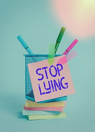 Text sign showing Stop Lying. Business photo text put an end on chronic behavior of compulsive or habitual lying Sticky note arrow banners stacked pads metal pens holder pastel background Stock Photo