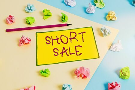Writing note showing Short Sale. Business concept for Home that is offered at a price that is less than the amount owed Colored crumpled papers empty reminder blue yellow clothespin
