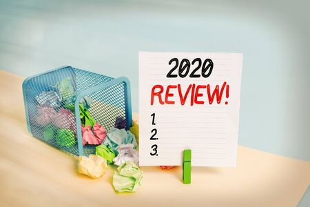 Conceptual hand writing showing 2020 Review. Concept meaning remembering past year events main actions or good shows Trash bin crumpled paper clothespin reminder office supplies