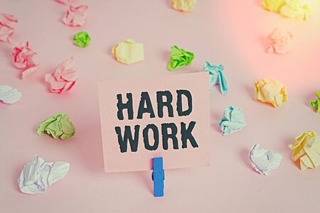 Text sign showing Hard Work. Business photo showcasing always putting a lot of effort and care into work or endurance Colored crumpled papers empty reminder pink floor background clothespin