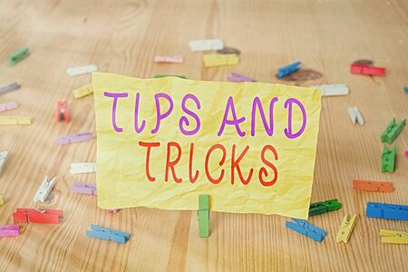 Writing note showing Tips And Tricks. Business concept for piece of inside facts specially in betting or investing Colored clothespin papers empty reminder wooden floor background office 写真素材