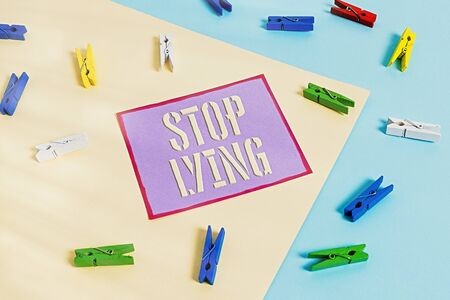 Handwriting text Stop Lying. Conceptual photo put an end on chronic behavior of compulsive or habitual lying Colored clothespin paper empty reminder yellow blue floor background office Stock Photo