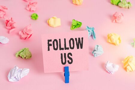 Text sign showing Follow Us. Business photo showcasing To invite a demonstrating or group to join his company and take rules Colored crumpled papers empty reminder pink floor background clothespin