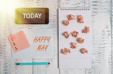 Word writing text Happy May. Business photo showcasing Happy new month Best wishes Fresh Start Celebrating Holiday Squared spiral notebook marker smartphone paper balls note clip wooden