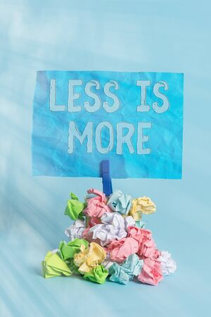 Conceptual hand writing showing Less Is More. Concept meaning used to express a minimalist approach is more effective. Reminder pile colored crumpled paper clothespin wooden space