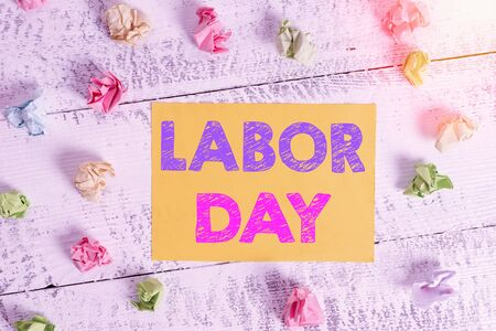Conceptual hand writing showing Labor Day. Concept meaning an annual holiday to celebrate the achievements of workers Crumpled rectangle squared paper reminder white wood desk Foto de archivo