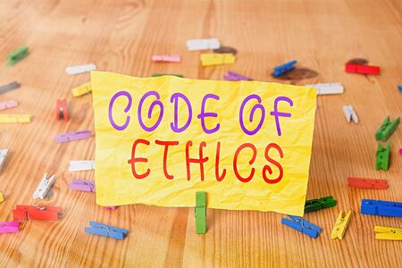 Writing note showing Code Of Ethics. Business concept for basic guide for professional conduct and imposes duties Colored clothespin papers empty reminder wooden floor background office