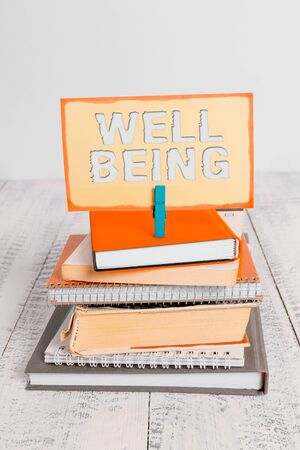 Handwriting text writing Well Being. Conceptual photo A good or satisfactory condition of existence including health pile stacked books notebook pin clothespin colored reminder white wooden