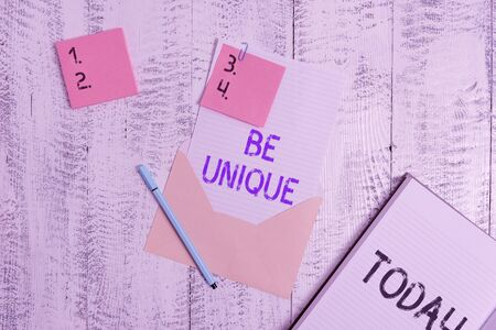 Writing note showing Be Unique. Business concept for being the only one of its kind Unlike anything else Incomparable Envelope sheet letter paper sticky notes pen notepad wooden background