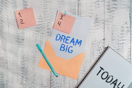 Writing note showing Dream Big. Business concept for seeking purpose for your life and becoming fulfilled in process Envelope sheet letter paper sticky notes pen notepad wooden background