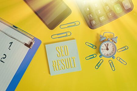 Word writing text Seo Result. Business photo showcasing the list created by search engines in response to a query Alarm clock clipboard clips smartphone calculator notepad color background