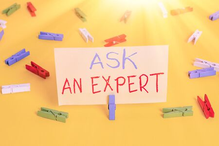 Word writing text Ask An Expert. Business photo showcasing consult someone who has skill about something or knowledgeable Colored clothespin papers empty reminder yellow floor background office