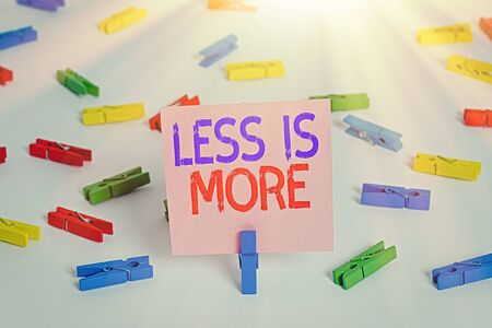 Writing note showing Less Is More. Business concept for used to express a minimalist approach is more effective. Colored clothespin papers empty reminder white floor background office