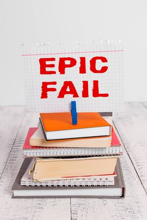 Writing note showing Epic Fail. Business concept for a spectacularly embarrassing mistake Humiliating situation pile stacked books notebook pin color reminder white wooden
