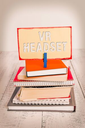 Handwriting text writing Vr Headset. Conceptual photo headmounted device that provides virtual reality for the wearer pile stacked books notebook pin clothespin colored reminder white wooden 写真素材
