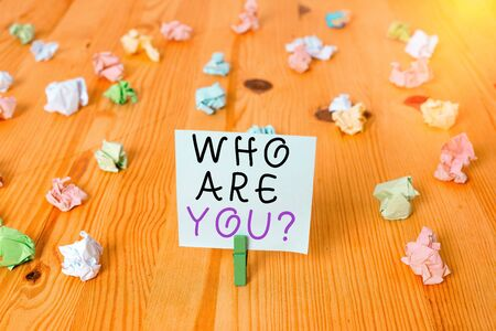 Handwriting text Who Are You Question. Conceptual photo asking about someone identity or demonstratingal information Colored crumpled papers empty reminder wooden floor background clothespin