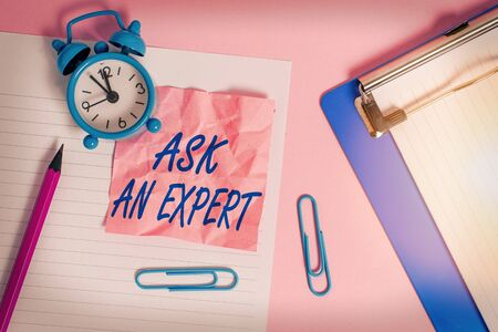 Text sign showing Ask An Expert. Business photo text consult someone who has skill about something or knowledgeable Paper sheet note clipboard pencil clips alarm clock colored background
