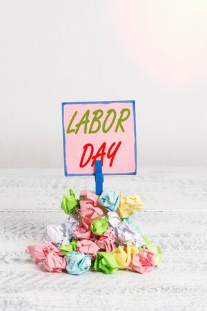 Text sign showing Labor Day. Business photo text an annual holiday to celebrate the achievements of workers Reminder pile colored crumpled paper clothespin reminder white wooden space