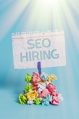 Word writing text Seo Hiring. Business photo showcasing employing a specialist will develop content to include keywords Reminder pile colored crumpled paper clothespin reminder blue background