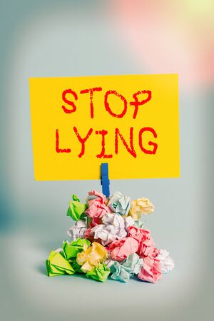 Word writing text Stop Lying. Business photo showcasing put an end on chronic behavior of compulsive or habitual lying Reminder pile colored crumpled paper clothespin reminder blue background Stock Photo