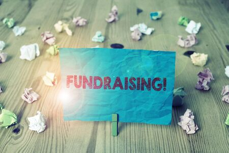 Word writing text Fundraising. Business photo showcasing seeking to generate financial support for charity or cause Colored crumpled papers empty reminder wooden floor background clothespin Reklamní fotografie