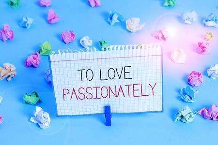 Handwriting text To Love Passionately. Conceptual photo Strong feeling for someone or something else Affection Colored crumpled papers empty reminder blue floor background clothespin