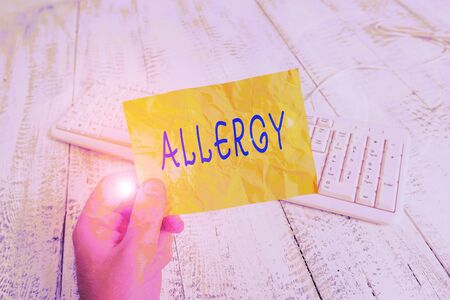 Text sign showing Allergy. Business photo showcasing Hypersensitive of the immune system towards particular substance man holding colorful reminder square shaped paper white keyboard wood floor