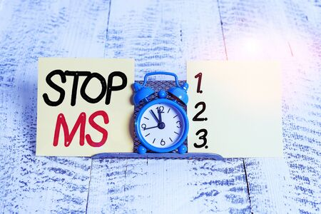 Text sign showing Stop Ms. Business photo text treat the condition that can affect the brain and spinal cord Mini blue alarm clock standing above buffer wire between two notation paper