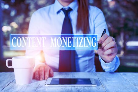 Conceptual hand writing showing Content Monetizing. Concept meaning making money from content that exists on your website Female business person sitting and holding mobile phone