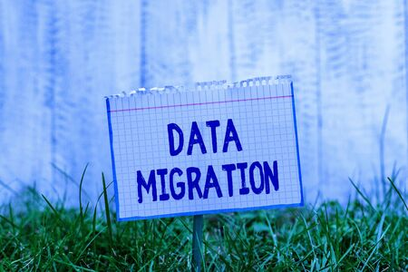 Word writing text Data Migration. Business photo showcasing process of transferring data between data storage systems Mathematic paper attached to a stick and placed in the green grassy land