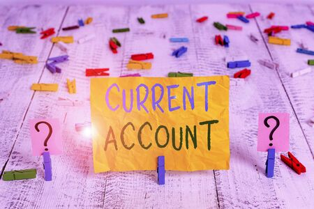 Conceptual hand writing showing Current Account. Concept meaning demonstrating bank account which can take out money any time Crumbling sheet with paper clips placed on the wooden table