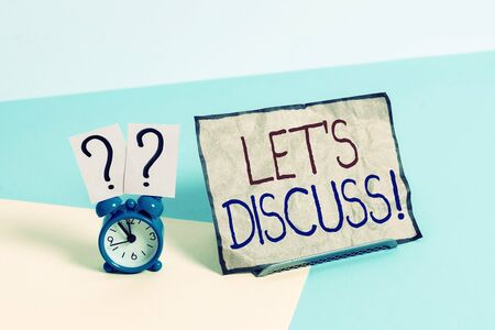 Writing note showing Let S Discuss. Business concept for asking someone to talk about something with demonstrating or showing Alarm clock beside a Paper sheet placed on pastel backdrop