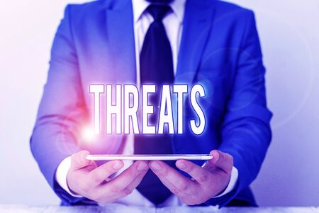 Word writing text Threats. Business photo showcasing Statement of an intention to inflict pain hostile action on someone Businessman in blue suite with a tie holds lap top in hands