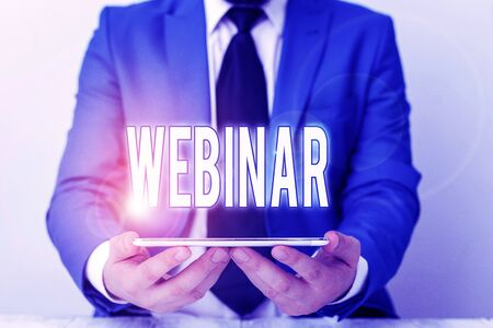 Word writing text Webinar. Business photo showcasing defined as seminar conducted over the Internet Web conferencing Businessman in blue suite with a tie holds lap top in hands