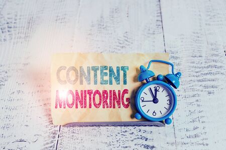Word writing text Content Monitoring. Business photo showcasing a tool to identify mentions of their organization Mini blue alarm clock stand tilted above buffer wire in front of notepaper Фото со стока