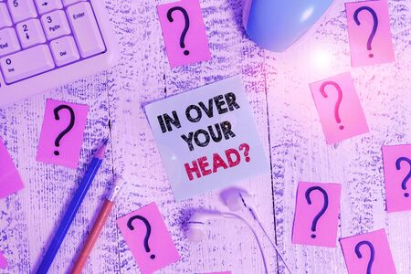 Conceptual hand writing showing In Over Your Head question. Concept meaning To be involved in a difficult situation problem Writing tools and scribbled paper on top of the wooden table