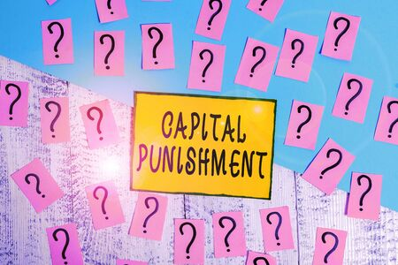 Word writing text Capital Punishment. Business photo showcasing authorized killing of someone as punishment for a crime Scribbled and crumbling papers with thick cardboard above wooden table