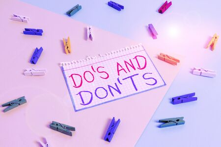 Writing note showing Do S And Don tS. Business concept for Rules or customs concerning some activity or actions Colored clothespin paper reminder with yellow blue background