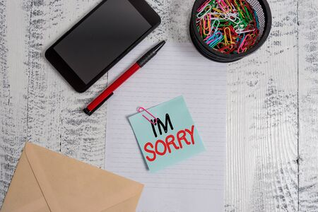 Handwriting text I M Sorry. Conceptual photo To ask for forgiveness to someone you unintensionaly hurt Smartphone paper sheet clips holder pen envelope note wooden background