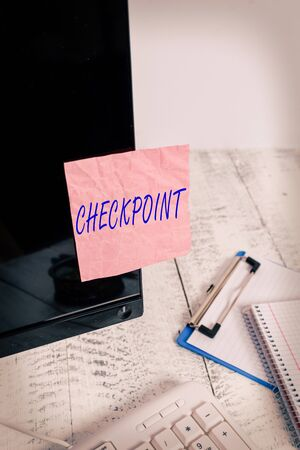 Text sign showing Checkpoint. Business photo text manned entrance, where travelers are subject to security checks Note paper taped to black computer screen near keyboard and stationary Stock Photo
