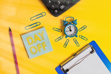 Writing note showing Day Off. Business concept for when you do not go to work even though it is usually a working day Alarm clock clipboard pencil calculator notepad colored background